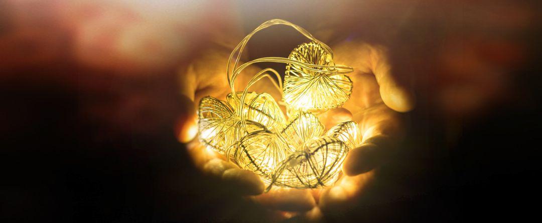 hands holding white heart shaped string light