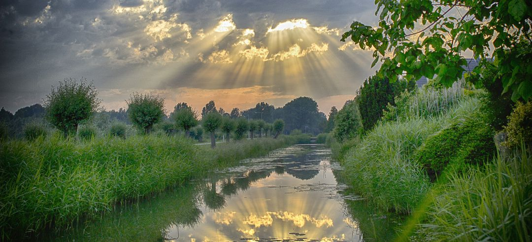 sun's rays bursting through clouds with re