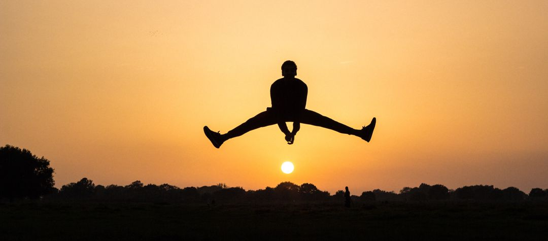 male figure jumping with legs splayed out to side, pointing to sunrise