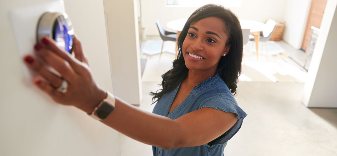 Woman changing dial on thermostat