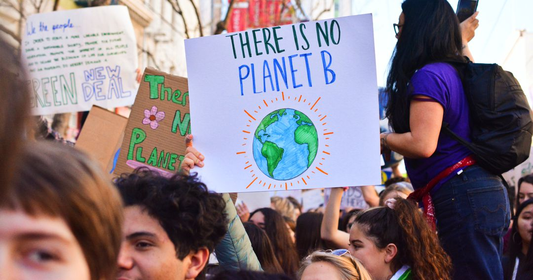 """Youth at a rally carring a sign """"there is no planet B"""" girl on platform holding microphone"""