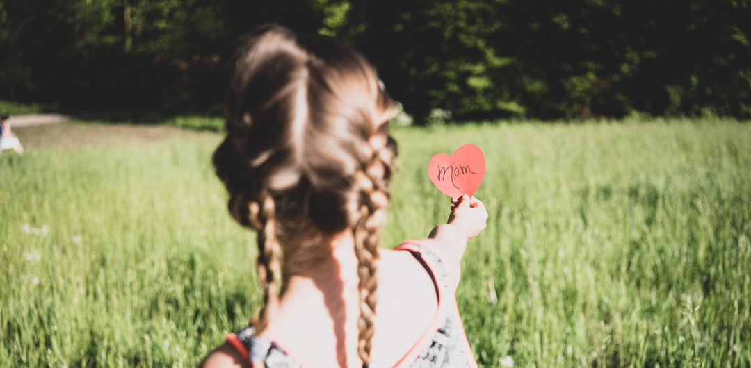"""little girl with braided pigtails standing in field with outstretched arm holding red paper heart with the word """"mom"""" on it"""