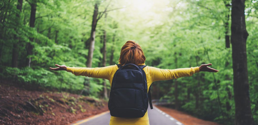 Woman standing in the middle of the road in forest wearing a backpack with arms spread wide breathing fresh air