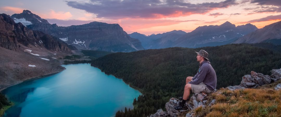 man sitting at the top of a mountain looking looking across vast scenery consisting of lake, forest, and mountains