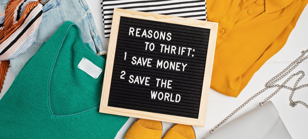 folded clothing with chalk board lying across clothes saying Reason to thrift: save money and save the world
