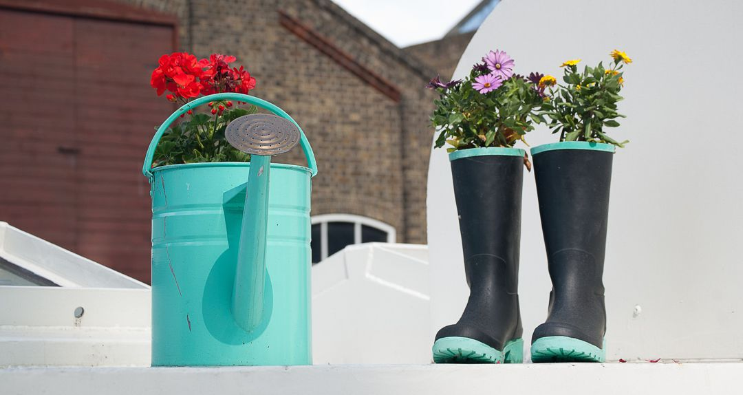 watering can and rubber boots with fresh cut flowers popping out of the top of each