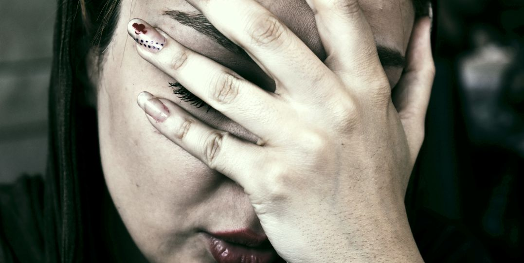 Woman covering eyes with her hand