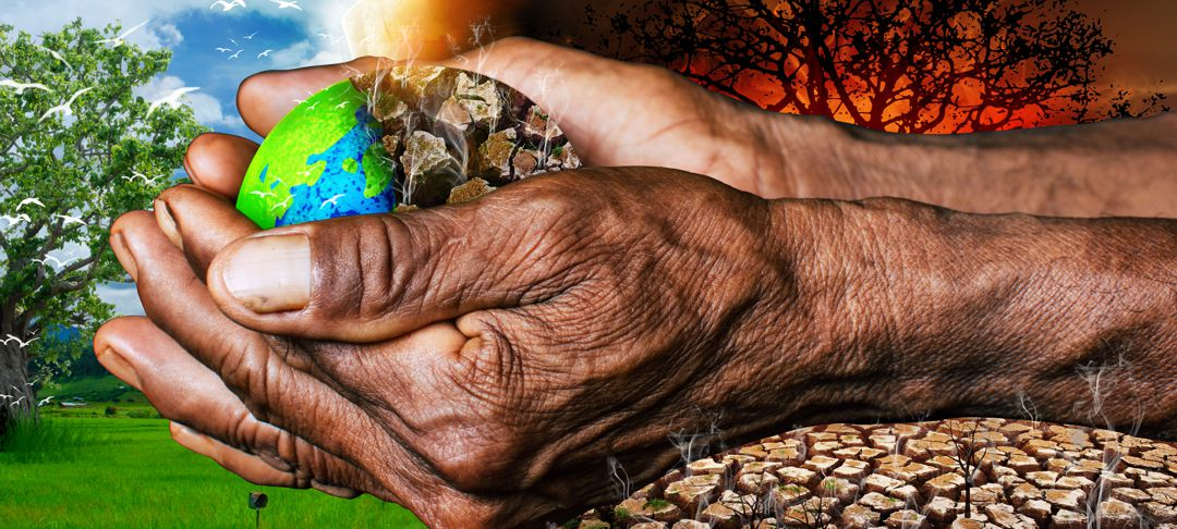 hands holding a small super imposed planet earth that is healthy on one side and dried up on the other