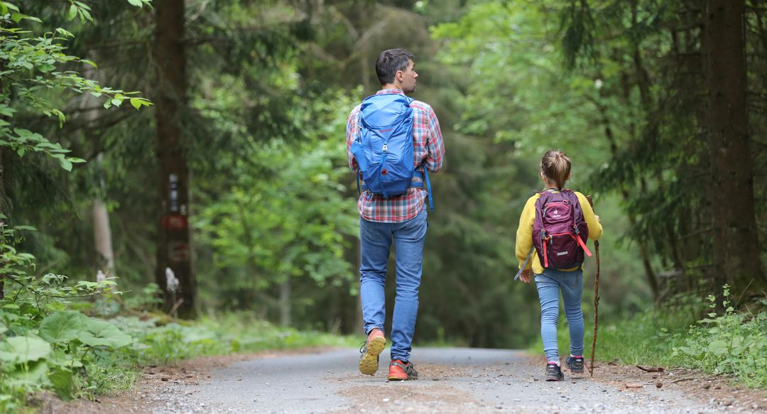 Man and little girl hiking with back packs